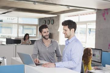 Zwei Kollegen mit Laptop in einem offenen Großraumbüro