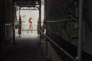 Deutschland, Niedersachsen, Hannover, junge weibliche Joggeinr auf einer Straße