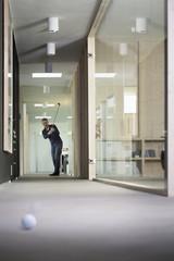Geschäftsmann beim Golfspielen im Korridor des Büros