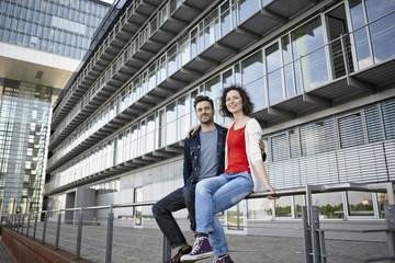 Deutschland, Nordrhein-Westfalen, Köln, Paar sitzt vor der Fassade im Rheinauhafen