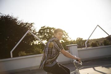 Teenager-Junge mit dem Fahrrad auf Parkplatz