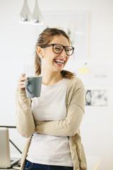 Frau mit Kaffeetasse im modernen Home-Office