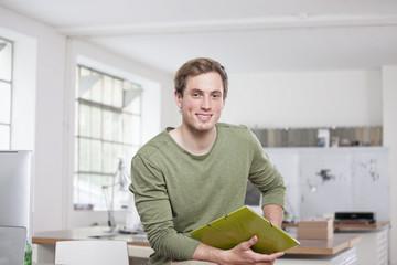 Lächelnde junge Frau Mann, auf Schreibtisch im Büro