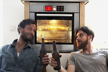 Zwei Männer prosten sich in der Küche zu