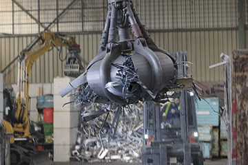 Greifer greift Schrott in einer Schrott-Recycling-Anlage