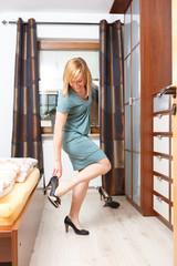 Frau, zieht Schuhe an im Schlafzimmer