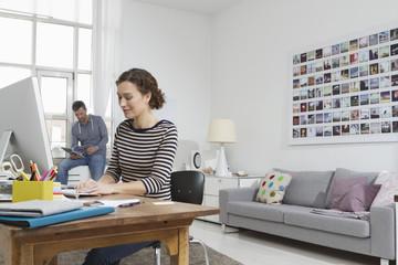 Mann und Frau zu Hause sitzen am Schreibtisch mit Computer