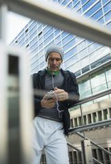 Sportlich, reifer Mann mit Kopfhörern und Smartphone