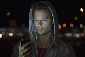 Junger Mann mit Kapuzenjacke, Musik hören in der Nacht