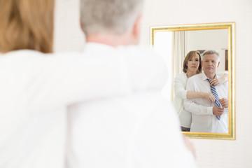 Spiegelbild, Frau bindet Krawatte für ihren Mann