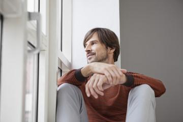Mann sitzt auf der Fensterbank, schaut aus dem Fenster