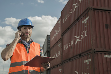 Mann mit Klemmbrett und Handy am Containerhafen