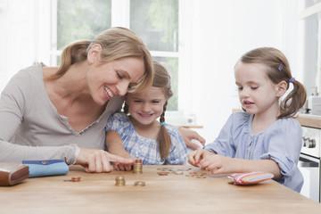 Mutter mit Töchtern beim Zählen, Stapel von Münzen