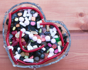 Colorful sweets in a heart-shape vase in a wooden background