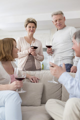 Zwei ältere Paare trinken Rotwein zu Hause
