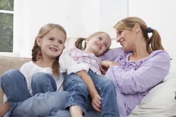 Mutter mit Töchtern auf Sofa
