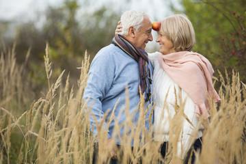 Portrait eines glücklichen Senior Paar, die Spaß mit einem Apfel