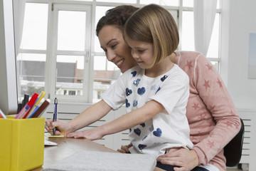 Mutter mit Tochter am Schreibtisch, Schreiben mit Kugelschreiber