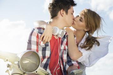 Teenager-Paar küssend auf Motorroller