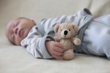 Porträt des schlafenden Babys, liegend auf Decke mit Teddy