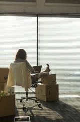 Geschäftsfrau mit Laptop, Füße auf Kartons