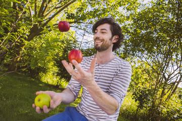 Mann beim Jonglieren mit Früchten im Garten