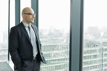 Zuversichtlicerh Geschäftsmann auf Büroetage schaut aus dem Fenster
