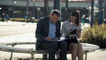 Business people working with tablet and documents on bench in th
