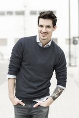 Lächelnder Mann mit Tätowierung auf seinem linken Arm