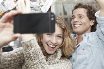 Portrait eines glücklichen jungen Paares mit Smartphone