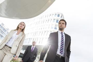 Geschäftsfrau und zwei Geschäftsleute unterwegs