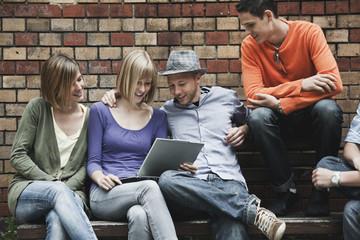Mann und Frau mit Laptop auf der Bank