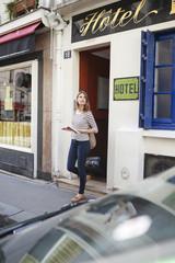 Frankreich, Paris, Porträt der jungen Frau mit Rollkoffer, beim Verlassen des Hotels