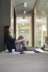 Porträt der Business-Frau sitzt auf dem Boden im Flur des Büro