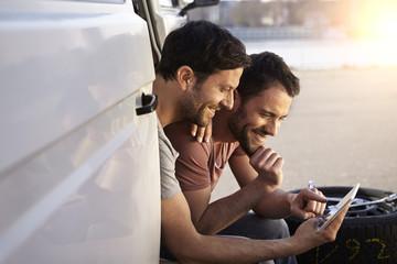 Zwei Männer sitzen im Auto, Blick auf Tablet-PC