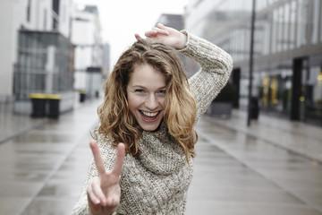 Portrait einer glücklichen jungen Frau zeigt Victory-Zeichen