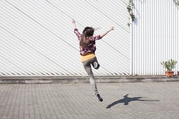 Ausgelassene junge Frau beim Springen im Freien