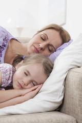 Mutter und Tochter schlafen auf Sofa