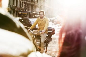 Deutschland, Nordrhein-Westfalen, Köln, junger Mann beim Fahrrad fahren