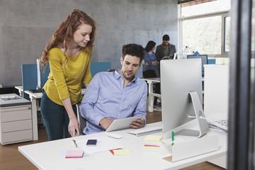 Vier Kollegen am Arbeitsplatz im GroßGroßraumbüro