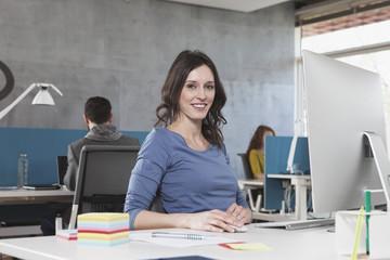 Lächelnde Frau an ihrem Arbeitsplatz im Büro