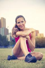 Sportive reife Frau sitzt im Park trainiert