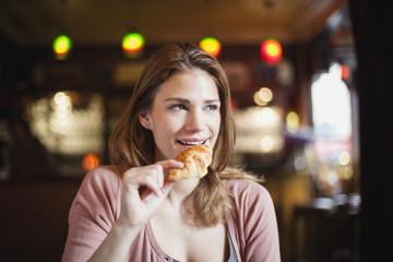 Frankreich, Paris, Porträt glücklicher junger Frau mit Croissant in einem Café