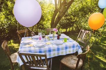 Partytisch im Garten mit Tellern und Gläsern
