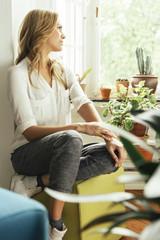 Junge Frau sitzt zwischen ihren Pflanzen zu Hause