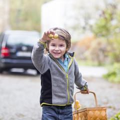 Kleiner Junge mit Korb, präsentiert seine gefunde Schokolade und Osterhase