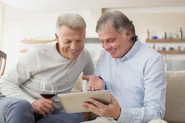 Zwei alten Freunde sitzen auf einer Couch im Wohnzimmer mit Tablet-Computer