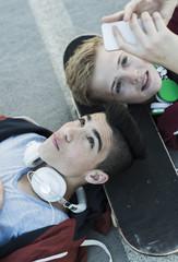 Zwei Jungen mit Handy und Kopfhörern liegen auf dem Boden