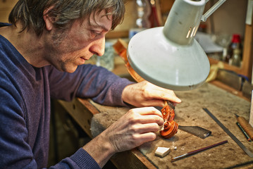 Geigenbauer in seiner Werkstatt bei Reparatur