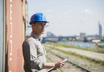 Mann mit blauem Schutzhelm, Prüfung von Frachtcontainern